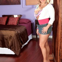 Dressed light-haired solo girl Anastasia Blake demonstrating cleavage in denim micro-skirt