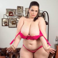 Fat solo female Mia Hottie disrobing down to pinkish melon-holder and panty set on couch