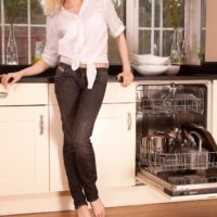 Elder fair-haired woman doing away with jeans in kitchen to toy furry gash in barefeet