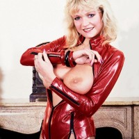 Mature platinum-blonde MILF Debbie Ashby looses her humungous juggs from a latex jacket in stockings