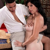 Senior brunette doll Raven Flight is undressed nude by her younger Latino paramour
