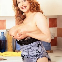 Red-haired MILF Ruth Tyler holds her big breasts while showing her fur covered cunny