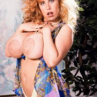Ginger-haired MILF Tabatha Towers lets out her enormous melons in over the knee pantyhose