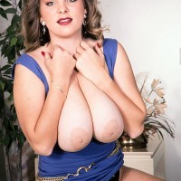 Solo female Rhonda Baxter sets her monster-sized tits and trimmed thicket free of dress in boots