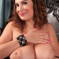 Solo female Valory Irene baring giant MILF boobies from fishnet bodystocking in stilettos