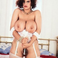 Solo model Nilli Willis seizes her monster-sized melons in white tights and garters