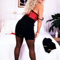 Solo model Taylor Marie holds her large juggs in a midbody cincher and garters with nylons