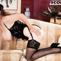 Solo model Traci Burr holds her hefty boobies in ebony lingerie and nylons with pumps
