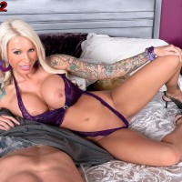 Inked blond MILF pornostar Lolly Ink letting out plump hooters for nip sucking
