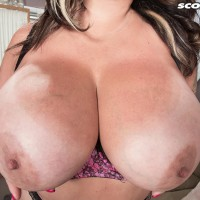 Tattooed brown-haired MILF Amaya May uncovers her large juggs from her bra in a microskirt
