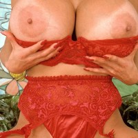 Top Japanese XXX adult star Minka baring her immense knockers from bra adorned red stockings