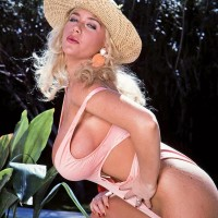 Top platinum-blonde X-rated star LA Squirt unsheathes her big juggs from swimsuit on poolside patio