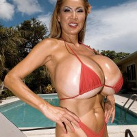 Top heavy Oriental solo female Minka greasing big bathing suit adorned boobs outdoors by pool