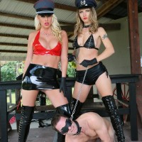 Two mistresses in hats and long boots lead masculine submissive by a leash