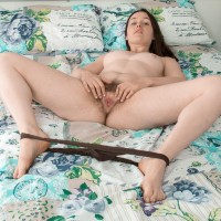 Amateur model Primrose Wood sets her hairy vag loose of panties on top of her bed