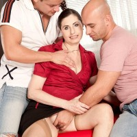 Experienced MILF Lorenzia has her twat and ass pawed by her junior lovers on a couch