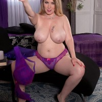 Sexy MILF Desiree sets her enormous titties loose of a violet sundress and bra in solo act