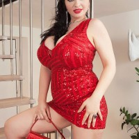 Black-haired model Joana Bliss sets her excellent boobies free of a short red dress in crimson high-heels