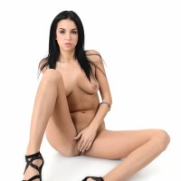 Brown-haired babe Foxxi Ebony strips to her stilettos before toying her smoothly-shaven muff