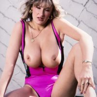 Legendary XXX film star Debbie Q sets her great breasts free of a taut dress in solo activity
