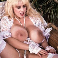 Well-known XXX film starlet Honey Moons extracts her gigantic boobies outdoors in garters and nylons