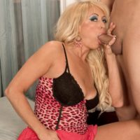 Tempting sandy-haired grandmother Natasha fellates on a big ebony dick after a seduction sequence in a mini-skirt