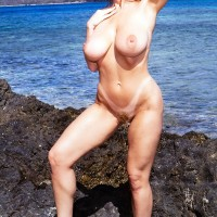 Light-haired solo female Danni Ashe rocks her amazing boobs while naked as the surf comes in