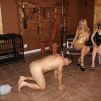 Kimber Forest and a stunning mistress urinate into a cup held by a collared masculine slave