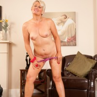 Mature platinum golden-haired uncovers her flat chest as she strips to heels on a leather stool