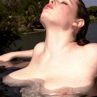 Solo model Desirae plays with her large breasts while spending time in the water