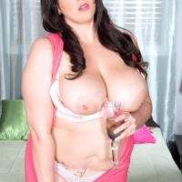 Plumper model Angel DeLuca sets her big titties free of a rosy sundress and brassiere in a bedroom