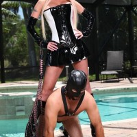 inviting fair-haired dominant Alexia Jordon straddles a hooded masculine submissive in latex by the pool