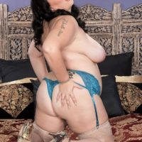 Black-haired BIG HOT WOMAN Charlotte Angel sets her immense boobs loose of lingerie on top of a bed