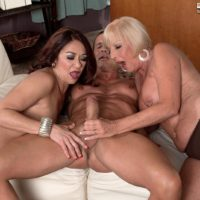 Older ladies Renee Black and Scarlet Andrews take turns slurping a hard cock
