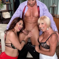 Older ladies Renee Black and Scarlet Andrews take turns slurping a hard cock