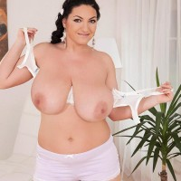 Solo female Juliana Simms wets down her large tits on a rubdown table in tight fitting cut-offs