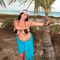 Thick chick Arianna Sinn uncups her melons as she gets naked by a tropical tree