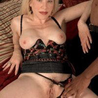 Sandy-haired grannie Jennifer Janes has her tits caressed while being disrobed by a ebony dude