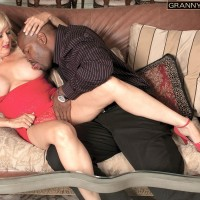 Light-haired granny Marina Johnson greets her ebony lover in crimson sundress and matching heels