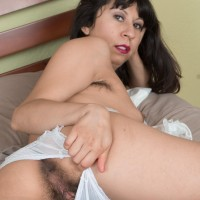 Brown-haired amateur Vivi Marie spreads her utter pubic hair on a bed in frilly white socks