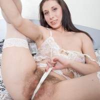 Black-haired pornostar Baby Boom unleashing hairy cunt from white panties in nylons