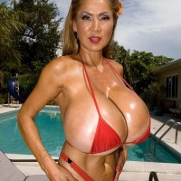 Huge-chested Japanese doll Minka models a pair bathing suits outdoors in close proximity to a pool