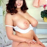 Plump brown-haired MILF Kerry Marie letting out large natural boobies from white boulder-holder