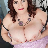 Plus sized solo female Roxee Robinson letting her large natural boobs loose from sundress in high heels