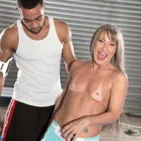 Fit senior lady Leilani Lei fellates her private trainer's ebony dick on a wrestling pad