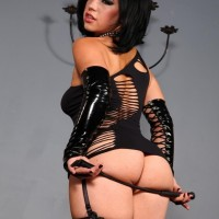 Uber-sexy dark-haired Belle Noir spanks her sweet butt with a whip in a revealing black dress