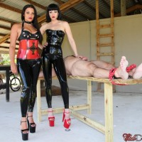 Spandex clad Dommes Jean Bardot and Michelle Lacy torture a confined masculine submissive