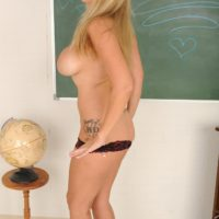 Aged light-haired broad garmented glasses strips naked in front of chalkboard in classroom