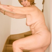 Senior redhead doffs a dress and pretties to pose downright nude on wooden stairs