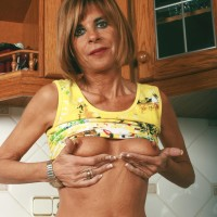Middle experienced housewife removes denim jeans and underwear to model nude in kitchen